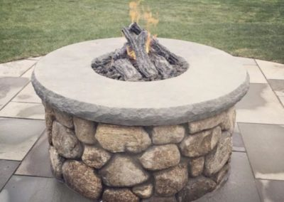 New England fieldstone fire pit with bluestone cap