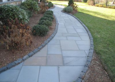 Bluestone walkway with black cobblestones border