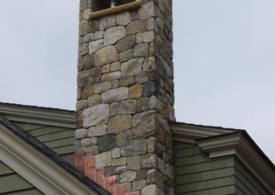 New England Fieldstone mosaic veneer chimney with limestone cap