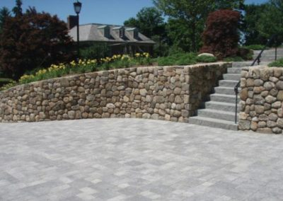 New England fieldstone rounds with granite steps and paver driveway