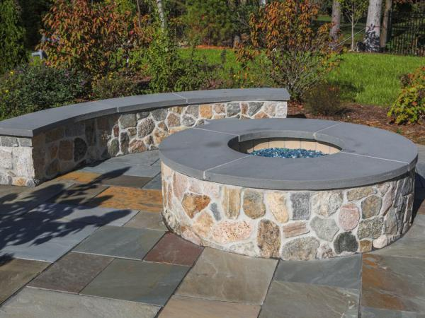 NE fieldstone mosaic firepit and seating wall with bluestone caps and patio