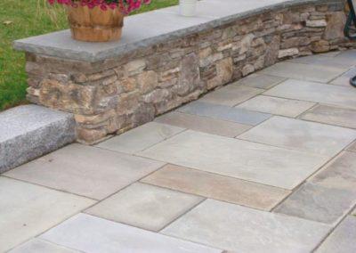 New England fieldstone wall with bluestone cap and natural cleft bluestone patio